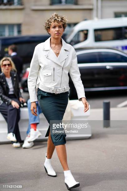 Guest wears earrings, necklaces, a white leather biker jacket, a dark green skirt, white pointy ankle-boots, outside Acne Studios, during Paris...