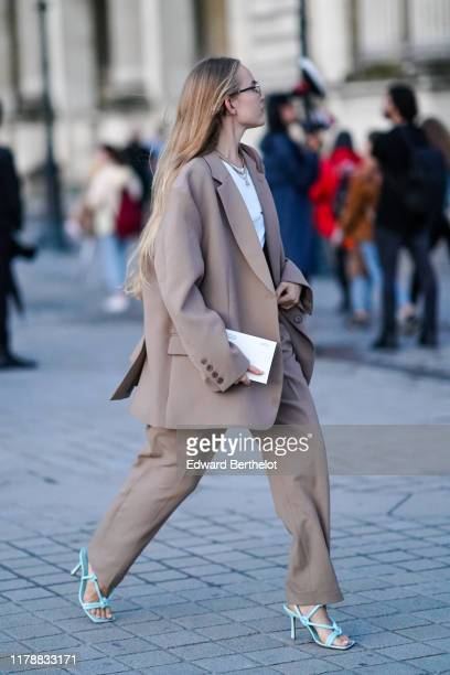 Guest wears earrings, necklaces, a white top, a light brown oversized pantsuit, blue heeled sandals, outside Louis Vuitton, during Paris Fashion Week...