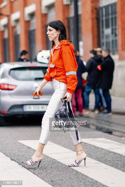 A guest wears earrings orange sunglasses an orange hooded windbreaker with grey inserts white crop pants a black Balenciaga beltbag an ankle chain...