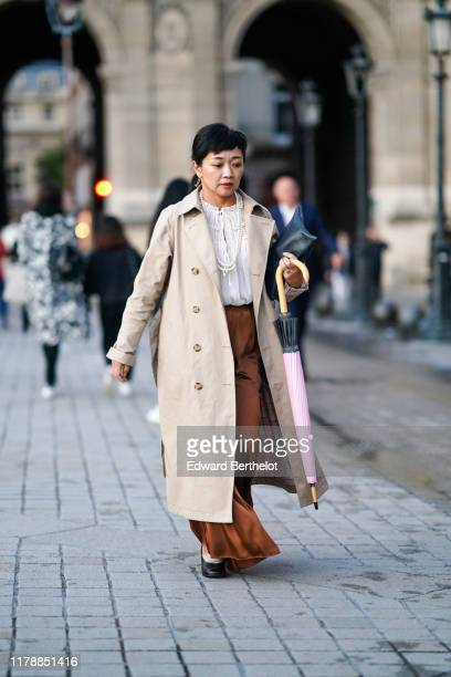 A guest wears earrings pearl necklaces a white frilly top a creamcolor trench coat lustrous brown flowing pants a darkgreen clutch black shoes and...