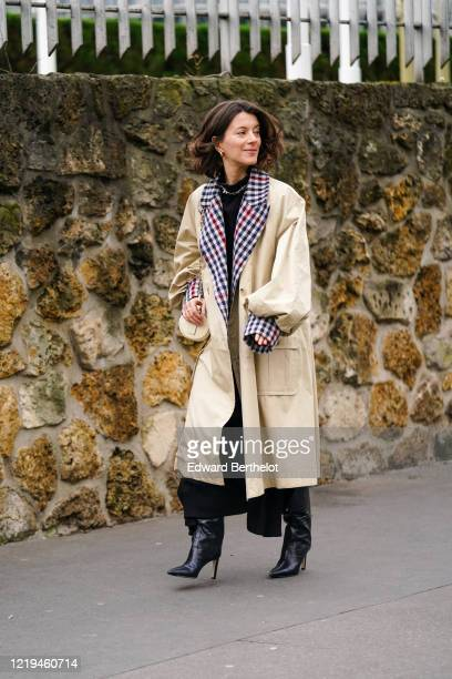 Guest wears earrings, rings, a necklace, a black cowl collar top, a beige oversized trench coat with puff sleeves, navy-blue and red checkered cuffs...
