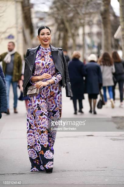 Guest wears earrings, rings, a watch, a black leather biker jacket, a glittering Bulgari bag, a purple and brown floral print full-length flowing...