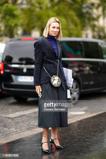 A guest wears earrings rings anklets a navy blue turtleneck a glittering heather navy blue jacket with lustrous black lapels a Chanel round canteen...