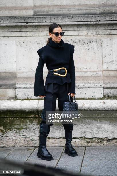 A guest wears earrings sunglasses a black cowl collar sleeveless top a black sweater with flare sleeves a black belt with a large goldtone buckle...