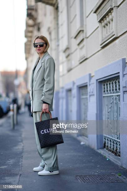 Guest wears earrings, sunglasses, a black top, a light green double-breasted jacket, matched pants, a Celine bag, white sneakers, outside MSGM,...