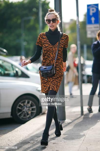 Guest wears earrings, sunglasses, a black turtleneck, a black bag, an orange and black tiger pattern V-neck short sleeves mini dress, black tights,...