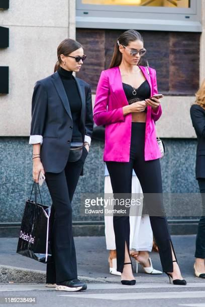 A guest wears earrings sunglasses a black turtleneck a navy blue jacket black flare pants black sneakers a black beltbag A guest wears mirrored...