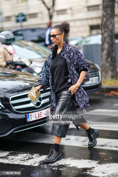 Guest wears earrings, sunglasses, a black V-neck sweater, a navy blue Balenciaga jacket with white chain pattern, black leather wide-legs short...