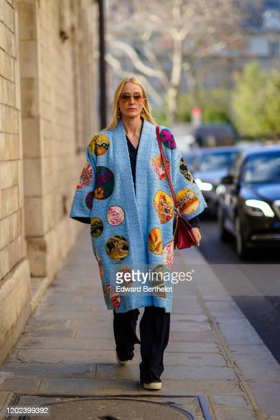 Guest wears earrings, sunglasses, a black v-neck top, black pants, a blue tweed kimono-style coat with round colorful patches, a red bag, sneakers,...