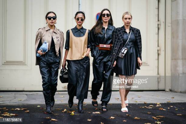 Guest wears earrings, sunglasses, a chain necklace, a taupe-color jacket, black leather pants, black pointy heeled boots, a blue clutch ; A guest...