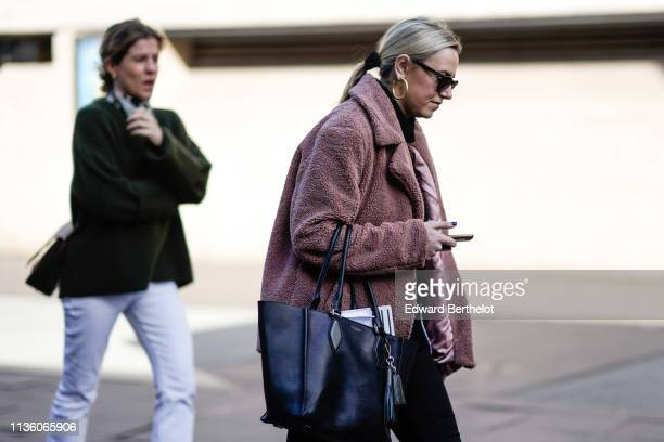 A guest wears earrings sunglasses a dusty pink fluffy jacket a black Michael Kors handbag during London Fashion Week February 2019 on February 17...