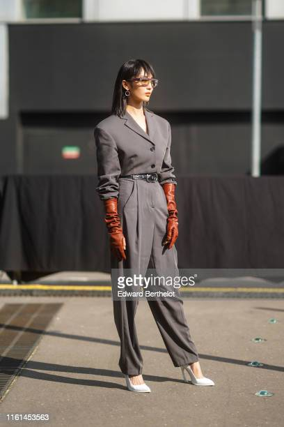 A guest wears earrings sunglasses a grey jumpsuit brown gloves a black belt white pointy heeled pumps outside Acne during Paris Fashion Week Haute...