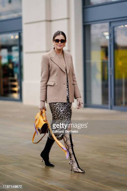 Guest wears earrings, sunglasses, a light brown jacket, a leopard print skirt, half-black and half- beige python pattern heeled boots, a yellow and...
