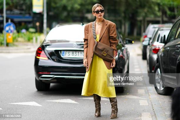 A guest wears earrings sunglasses a lustrous yellow dress with a large neck necklaces a brown Fendi crossbody bag a caramelcolor oversized jacket...