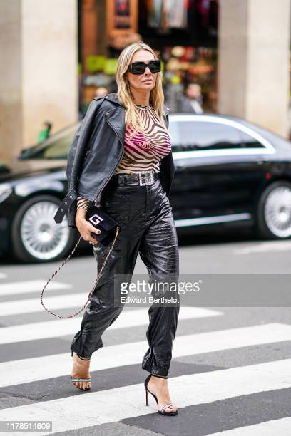 A guest wears earrings sunglasses a necklace a zebra pattern long sleeves top a black leather biker jacket a transparent vinyl belt with a rhinestone...