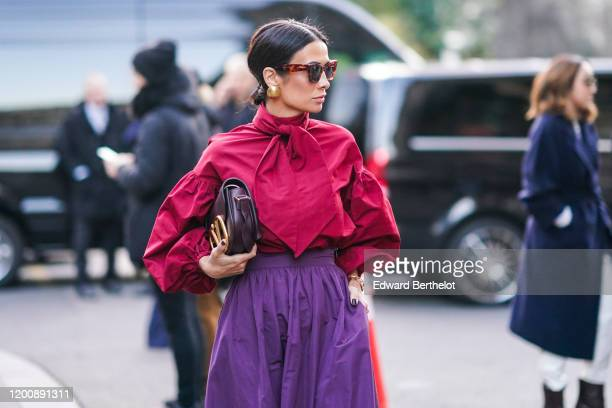 A guest wears earrings sunglasses a red blouse with puff sleeves and a lavaliere a Valentino bag a purple gathered skirt outside Ralph Russo during...