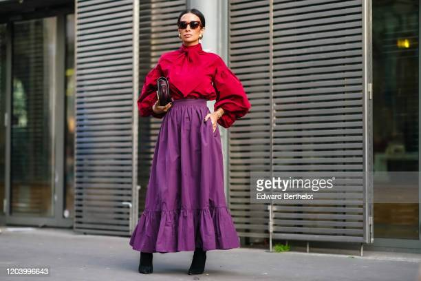 Guest wears earrings, sunglasses, a red blouse with puff sleeves and a lavaliere, a Valentino bag, a purple gathered and ruffled long skirt, black...