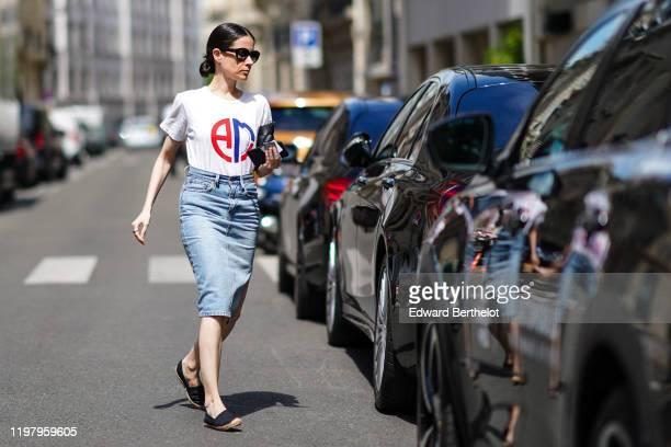 A guest wears earrings sunglasses a white AMI tshirt blue denim skirt black espadrilles a black clutch outside Bode during Paris Fashion Week...