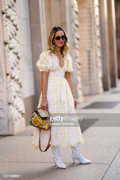 Guest wears earrings, sunglasses, a white and yellow dress with embroidery, a Loewe bag, white pointy leather boots, outside Vivetta, during Milan...