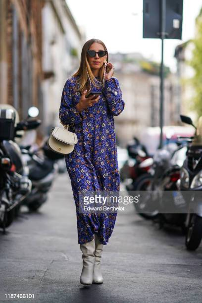 Guest wears earrings, sunglasses, a white bag, white pointy boots, a floral print long sleeves blue dress, outside the Blumarine show during Milan...