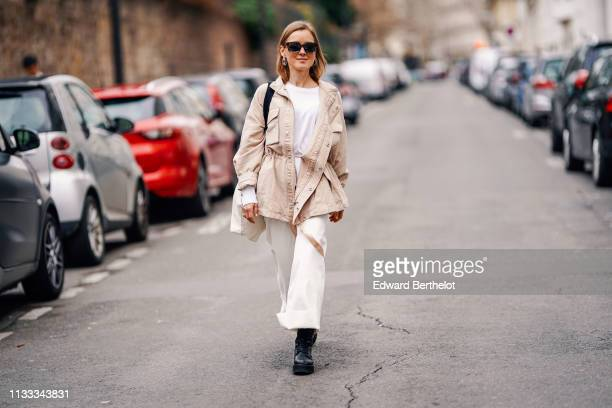 A guest wears earrings sunglasses a white top a beige jacket a white bag with a black strap white wideleg cuffed pants black platform shoes outside...