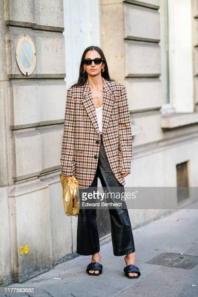 A guest wears earrings sunglasses a white top a brown and black checkered oversized jacket black leather flare pants black woven leather mules a...
