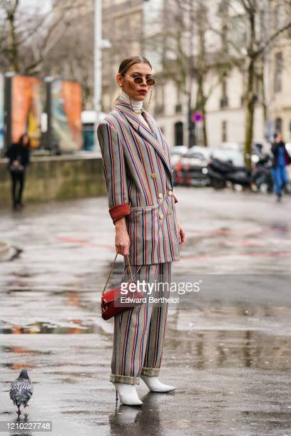 Guest wears earrings, sunglasses, a white turtleneck, a grey double-breasted jacket with red and blue stripes and brass buttons, matched pants with...