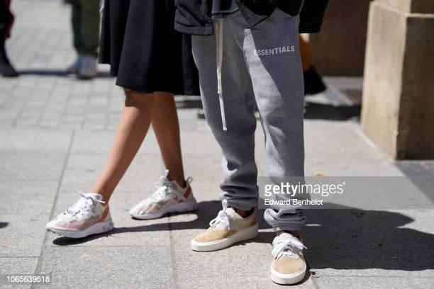 A guest wears Essential gray sportswear pants sneakers shoes outside Louis Vuitton during Paris Fashion Week Menswear SpringSummer 2019 on June 21...