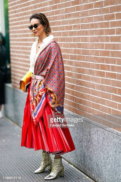 Guest wears Fendi sunglasses, necklaces, a white lace shirt, a yellow clutch, a colorful Fendi scarf, a pale pink Fendi belt, a red leather pleated...