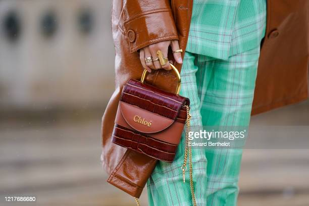 Guest wears finger rings, a burgundy leather crocodile pattern Chloe bag with golden metallic handle and chains, green checked pants, outside Ann...