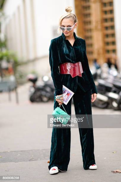 A guest wears flare pants and a green chanel bag outside Valentin Yudashkin during Paris Fashion Week Womenswear Spring/Summer 2018 on October 2 2017...