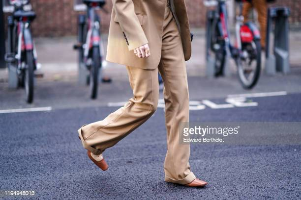 A guest wears flare pants pointy brown leather shoes during London Fashion Week September 2019 on September 16 2019 in London England