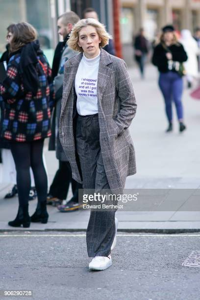 A guest wears flare pants white sneakers a white tshirt during London Fashion Week Men's January 2018 at on January 7 2018 in London England