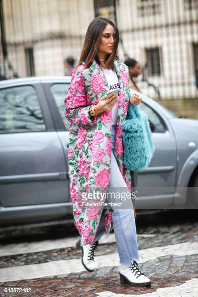 A guest wears flower print coat denim jeans pants and white shoes and a blue fur bag outside the Giambattista Valli show during Paris Fashion Week...