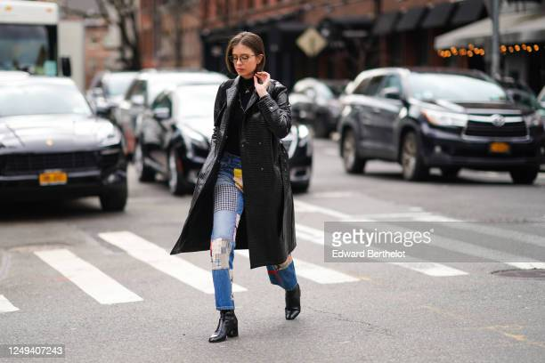 Guest wears glasses, a black leather crocodile pattern coat, blue patchwork denim jeans, black leather pointy shoes, a black top, a necklace, outside...