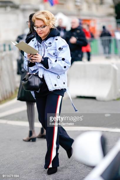 A guest wears glasses a blue denim jacket with polka dots a hood sportswear striped pants black shoes outside Chanel during Paris Fashion Week Haute...