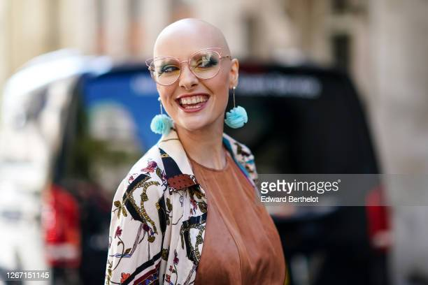 A guest wears glasses a blue ruffled earrings a brown silky lustrous flowing dress during London Fashion Week September 2019 on September 13 2019 in...