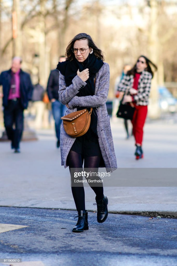 A guest wears glasses, a brown bag, a coat, a black dress, a scarf, tights, black leather shoes, outside Chanel, during Paris Fashion Week -Haute Couture Spring/Summer 2018, on January 23, 2018 in Paris, France.