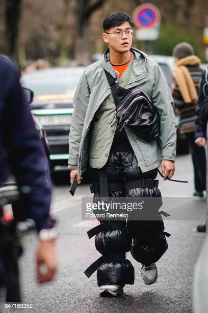 A guest wears glasses a gray jacket black shiny pants with straps a black shoulder strap bag outside Dior during Paris Fashion Week Menswear Fall...