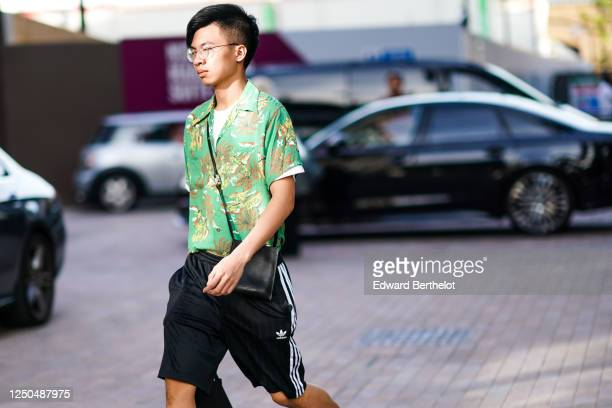 Guest wears glasses, a green floral print shirt, a black bag, Adidas shorts, during London Fashion Week September 2019 on September 14, 2019 in...