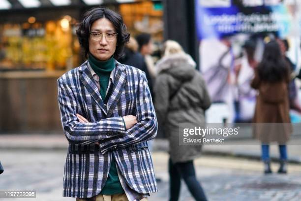 A guest wears glasses a green turtleneck a blue and black blazer jacket with checked printed pattern beige pants shoes during London Fashion Week...