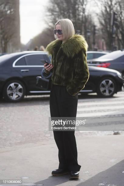 A guest wears glasses a green/khaki fluffy faux fur coat a rectangular shiny black bag outside Chanel during Paris Fashion Week Womenswear...
