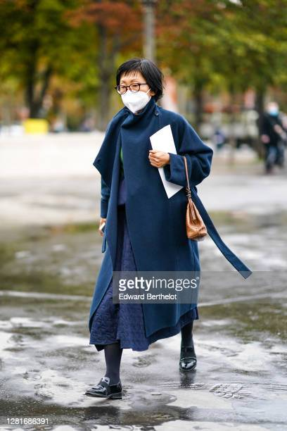 Guest wears glasses, a navy blue dark long wool coat, a brown leather bag, black shiny leather shoes, outside Chanel, during Paris Fashion Week -...