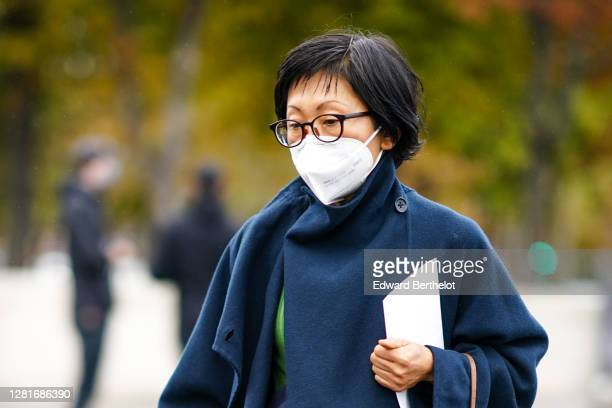 Guest wears glasses, a navy blue dark long wool coat, outside Chanel, during Paris Fashion Week - Womenswear Spring Summer 2021, on October 06, 2020...