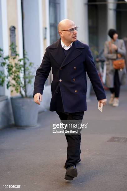 Guest wears glasses, a navy blue double breatsed jacket, black pants, outside Tod's, during Milan Fashion Week Fall/Winter 2020-2021 on February 21,...