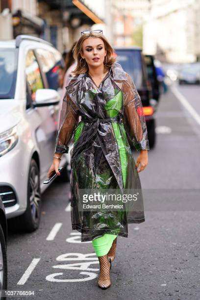 A guest wears glasses a plastic transparent trench coat over a green dress fishnet tights shoes during London Fashion Week September 2018 on...