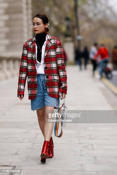 A guest wears glasses a red and white checked blazer jacket a white shirt a black turtleneck blue denim short red shoes during London Fashion Week...