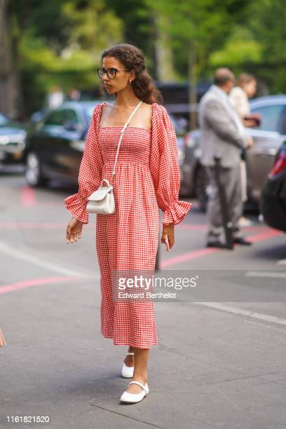Guest wears glasses, a red gingham checked dress, a white bag, white shoes, during Paris Fashion Week -Haute Couture Fall/Winter 2019/2020, on July...