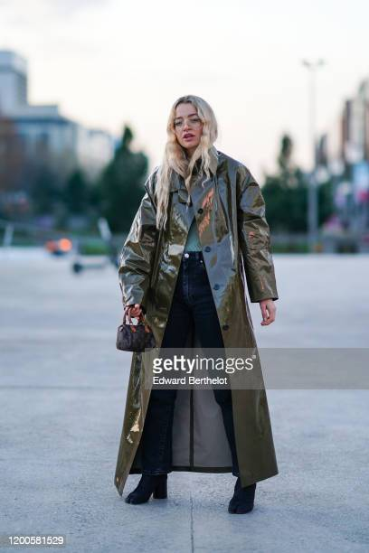 Guest wears glasses, a shiny khaki vinyl long trench coat, navy-blue jeans, black suede Tabi split-toe boots with block heels, a small Louis Vuitton...