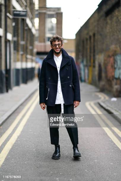 A guest wears glasses a white shirt a navy blue jacket black pants leather shoes during London Fashion Week Men's January 2020 on January 04 2020 in...